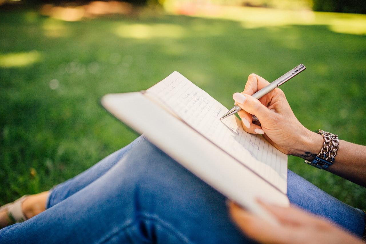 osoba pisząca w notesie